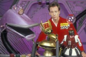 Joel and the bots. Gypsy in purple, Crow T. Robot in gold, Tom Servo in red.